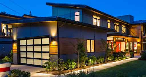 a lit modern house with HQI installed garage door